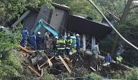 土砂崩れがあった民家の捜索をする消防隊員ら=北海道厚真町で2018年9月6日午前7時半、竹内幹撮影