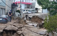 道路が亀裂し、押し寄せた泥に覆われた住宅地=札幌市清田区里塚で2018年9月6日午前9時52分、土谷純一撮影