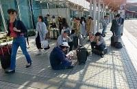 飛行機の発着が止まった新千歳空港ターミナルビルの前で待機する旅行客ら=北海道千歳市で2018年9月6日午前、阿部義正撮影