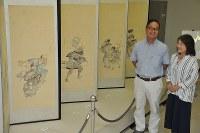 寄贈した「市井風俗図屛風」を前にする若林泰典さん、久仁子さん夫妻広島県福山市西町2の広島県立歴史博物館で2018年9月6日午前11時7分、松井勇人撮影