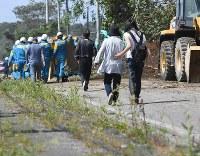 発見され運ばれる身元不明者の後を追う、家族とみられる人たち=北海道厚真町で2018年9月6日午前11時29分、竹内幹撮影