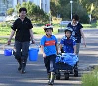 川の水を家に持って帰る家族連れ=北海道厚真町で2018年9月6日午後4時14分、竹内幹撮影
