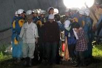 地震による土砂崩れで家が倒壊し、3人の捜索が続いていた現場で、助け出された滝本舞樺さん(16)の遺体を確認し涙ぐむ兄天舞(てんま)さん(17)=北海道厚真町で2018年9月6日午後7時45分、和田大典撮影