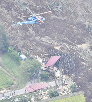 Rescue workers and other authorities search for people near a house hit by a landslide caused by an earthquake in the town of Atsuma, Hokkaido, on Sept. 7, 2018. (Mainichi)