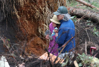 Two people cling to each other after their family member was found dead near a site hit by a landslide caused by an earthquake in the town of Atsuma, Hokkaido, on Sept. 7, 2018. (Mainichi)