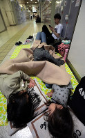 Hinata Kurahashi, 9, left, and her younger sister Minato, 5, sleep on the floor of JR Sapporo Station in Sapporo's Chuo Ward, on Sept. 7, 2018. The sisters and her father Yuki, 38, stayed at the station overnight because an evacuation center near their house was full. Yuki said,