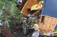 Rescue workers search for people near a house hit by a landslide caused by an earthquake in the town of Atsuma, Hokkaido, on Sept. 7, 2018. (Mainichi)