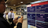 A Chinese tourist takes photos on a noticeboard written in foreign languages that informs passengers of the suspension of train services due to an earthquake at JR Sapporo Station in Sapporo's Kita Ward, on Sept. 7, 2018. (Mainichi)