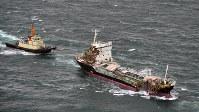 関西国際空港沖から明石海峡を通りえい航されるタンカー(右)=明石海峡で2018年9月7日午前7時22分、本社ヘリから加古信志撮影