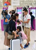 国内線の運航が一部再開され、搭乗手続きをする家族連れ=関西国際空港で2018年9月7日午前10時28分、山田尚弘撮影