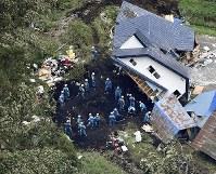 地震による土砂崩れで倒壊した建物を捜索する警察官ら=北海道厚真町で2018年9月7日午前8時38分、本社ヘリから