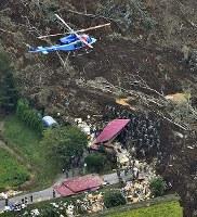 地震による土砂崩れで倒壊した建物の周辺を捜索する自衛隊員ら=北海道厚真町で2018年9月7日午前9時7分、本社ヘリから