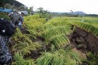 地震で大きな亀裂ができた田んぼを歩き、安否不明者の捜索へ向かう自衛隊員=北海道厚真町で2018年9月7日午前7時12分、和田大典撮影
