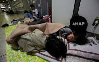 JR札幌駅で一夜を明かす家族連れ。札幌市中央区の美容師・倉橋佑樹さん(38)は近所の避難所がいっぱいで入れず、6日午後7時半頃からここで過ごす。長女陽さん(9歳・手前左)と次女湊ちゃん(5歳・右)が寄り添って寝ていた。倉橋さんは「自宅は停電と断水で生活できない。ガスは通っているが食事は昨晩食べたカップラーメンだけ。早く復旧してほしい」と話した=札幌市中央区で2018年9月7日午前6時10分、貝塚太一撮影