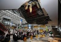 国内線の運航が再開した新千歳空港のターミナルビル内で、天井の一部が落下した付近で出発便を待つ多くの観光客ら=北海道千歳市で2018年9月7日午後1時51分、貝塚太一撮影