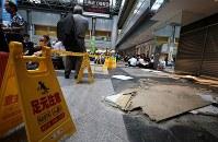 国内線の運航が再開した新千歳空港のターミナルビル内で、出発便を待つ多くの観光客らの付近に落下した天井の一部=北海道千歳市で2018年9月7日午後1時55分、貝塚太一撮影
