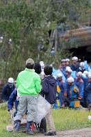地震による土砂崩れに襲われた家で見つかった滝本芳子さんとみられる女性が救急車に運ばれるのを見つめる親族=北海道厚真町で2018年9月7日午後2時9分、和田大典撮影