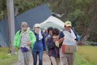 滝本芳子さんとみられる女性が見つかった現場から沈痛な表情で引き上げる息子の文夫さん(右端)ら親族=北海道厚真町で2018年9月7日午後2時22分、和田大典撮影