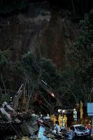 日没が迫り、照明の灯りの下で安否不明者の捜索を続ける警察や自衛隊員ら=北海道厚真町で2018年9月7日午後5時49分、和田大典撮影