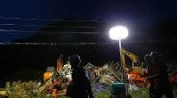 投光器を使って土砂崩れ現場で安否不明者の捜索活動が続いた=北海道厚真町で2018年9月7日午後6時14分、長谷川直亮撮影