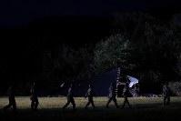 地震による土砂崩れ発生から2日目の日没後も、照明の灯りの下、安否不明者の捜索を続ける現場に向かう自衛隊員ら=北海道厚真町で2018年9月7日午後6時20分、和田大典撮影