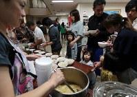 地元商店が寄付した食材で商工会が作った豚汁や、自衛隊が炊いたご飯などを受け取る被災者ら=北海道厚真町で2018年9月7日午後6時35分、貝塚太一撮影