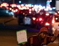給油をするため行列する車。ガソリンスタンドの職員が「在庫切れ」を知らせていた=札幌市清田区で2018年9月7日午後6時35分、竹内幹撮影