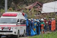 地震による土砂崩れが起きた現場で救助された人を救急車に乗せる警察官ら=北海道厚真町で2018年9月7日午後1時37分、和田大典撮影