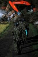 日没後も、照明の光の下、安否不明者の捜索が続く現場へ向かう自衛隊員=北海道厚真町で2018年9月7日午後6時12分、和田大典撮影