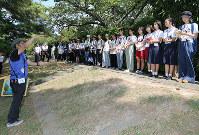 広村堤防で語り部の熊野享さん(左端)から説明を受ける高校生たち=和歌山県広川町広で、山本芳博撮影
