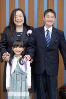 入学式前に自宅の玄関前で記念写真に納まる及川真乃愛さん(左下)と兄翔世さん(右)、母ゆかりさん。翔世さんも今年中学生になり、ゆかりさんの相談相手になれるほど成長した=宮城県南三陸町で2018年4月9日、喜屋武真之介撮影