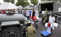 自衛隊の給水車に並ぶ被災者=北海道厚真町の総合福祉センターで2018年9月8日午前8時13分、長谷川直亮撮影