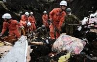 多くの日用品が掘り出される土砂崩れ現場で安否不明者の捜索をする消防隊員や自衛隊員=北海道厚真町で2018年9月8日午前7時59分、貝塚太一撮影
