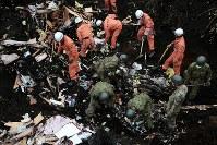 多くの日用品が掘り出される土砂崩れ現場で、安否不明者の捜索をする自衛隊員と消防隊員=北海道厚真町で2018年9月8日午前7時53分、貝塚太一撮影