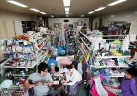 電力供給が再開した市街地の事務用品店。地震で商品が散乱した店舗内を片付け、親族13人で居住スペースをつくって生活している=北海道厚真町で2018年9月8日午前10時、貝塚太一撮影