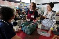 電力供給が再開し、購入制限を設けて営業を始めた市街地のスーパーマーケット。買い物客と店員が笑顔で互いを励まし合った=北海道厚真町で2018年9月8日午前10時59分、貝塚太一撮影