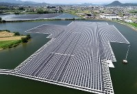 注目を集める再生可能エネルギー。中でも太陽光発電は増加傾向にあり、近年では、ため池にソーラーパネルを浮かべた発電所も稼働している。水不足対策としてため池が多く造られてきた香川県さぬき市。「東王田池ソーラー発電所」(設置面積約4万平方㍍)が7月から運転を始めた。日本アジア投資(東京都千代田区)が中心となって設置し、年間発電量は一般家庭約680世帯分に相当する約301万キロワット時を見込む。大規模な太陽光発電所を巡っては、造成工事による周辺環境への影響も懸念される。ため池はそういった工事が不要で、周辺に日光を遮るものもなく、機器類の冷却効果も高い。効率よく電気を生み出すと期待される=香川県さぬき市で2018年8月30日、小型無人機で山崎一輝撮影