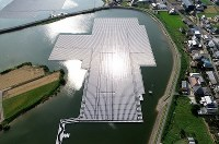 太陽の光が反射する東王田池ソーラー発電所=香川県さぬき市で2018年8月30日、小型無人機で山崎一輝撮影