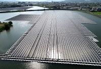 60本の強力なワイヤーロープでため池の底と固定されて浮く東王田池ソーラー発電所=香川県さぬき市で2018年8月30日、小型無人機で山崎一輝撮影