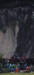 薄暮の中、安否不明者の捜索活動を続ける警察官や消防隊員ら=北海道厚真町で2018年9月8日午後5時48分、貝塚太一撮影