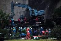 薄暮の中、災害救助犬が入り活動が続く安否不明者の捜索現場=北海道厚真町で2018年9月8日午後5時48分、貝塚太一撮影