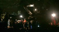 投光器を使って安否不明者の捜索活動を続ける警察官や消防隊員ら=北海道厚真町で2018年9月8日午後6時39分、貝塚太一撮影