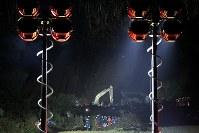 地震で土砂崩れが発生した現場(奧)で、照明を照らし、夜通し安否不明者の捜索を続ける自衛隊や消防隊ら=北海道厚真町で2018年9月8日午後8時31分、和田大典撮影