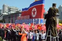 「栄光ある我が祖国」などと書かれたスローガンを前に、建国70周年を祝う市民たち=2018年9月9日、平壌で渋江千春撮影