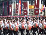 「自力更生」と書かれたスローガンを前に行進する参加者ら=2018年9月9日、平壌で渋江千春撮影