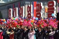 パレードに参加し、花や旗を振って歓声を挙げる市民たち=2018年9月9日、平壌で渋江千春撮影