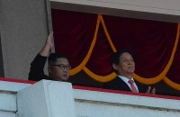 手を挙げて観衆に応える北朝鮮の金正恩朝鮮労働党委員長(左)と中国の栗戦書・全国人民代表大会常務委員長(国会議長)=2018年9月9日、平壌で渋江千春撮影