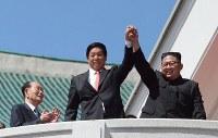 パレード終了後、手を取り合って観衆に応える北朝鮮の金正恩朝鮮労働党委員長と中国の栗戦書・全国人民代表大会常務委員長(国会議長)=2018年9月9日、平壌で渋江千春撮影
