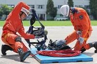 「障害突破」種目の訓練の中で、空気呼吸器やロープを素早く装着する隊員=東大阪市の大阪市消防局高度専門訓練センターで、三村政司撮影