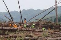 地震による大規模な土砂崩れが起き、大量の木や土砂に埋まった現場で安否不明者を捜索する消防隊員ら=北海道厚真町幌内で2018年9月9日午後2時29分、和田大典撮影